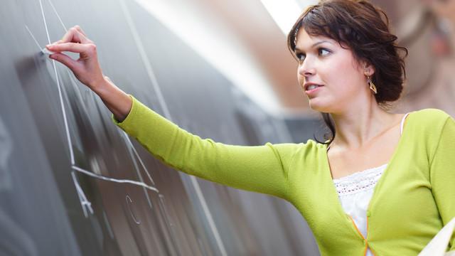 a female teacher drawing a diagram on a chalkboard